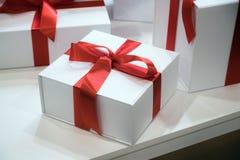 圣诞节或生日时间 有红色丝带的礼物盒在木书桌背景 免版税库存照片