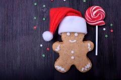 圣诞节戴圣诞老人项目帽子的姜饼人 库存照片