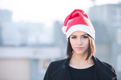 圣诞节户外圣诞老人帽子妇女微笑的画象 戴她的圣诞老人帽子有城市都市背景的微笑的愉快的女孩 愉快 免版税库存照片