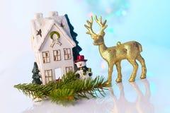 圣诞节房子和驯鹿与bokeh光 免版税库存图片