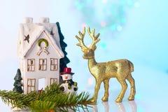 圣诞节房子和驯鹿与bokeh光 库存照片