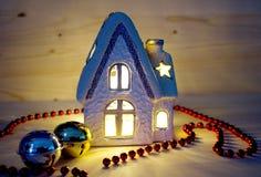 圣诞节房子烛台和红色圣诞节链子和两个门铃 免版税库存照片