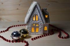 圣诞节房子烛台和红色圣诞节链子和两个门铃 免版税库存图片