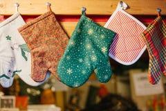 圣诞节手套握持热锅的布垫子在厨房里垂悬以模糊的厨房器具为背景 免版税图库摄影