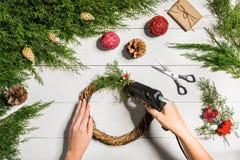 圣诞节手工制造diy背景 做工艺xmas花圈和装饰品 白色木桌顶视图与女性的 库存照片
