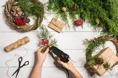 圣诞节手工制造diy背景 做工艺xmas花圈和装饰品 白色木桌顶视图与女性的 免版税库存照片