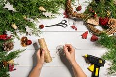圣诞节手工制造diy背景 做工艺xmas花圈和装饰品 白色木桌顶视图与女性的 库存图片