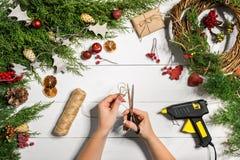 圣诞节手工制造diy背景 做工艺xmas花圈和装饰品 白色木桌顶视图与女性的 免版税库存图片