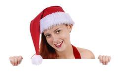圣诞节拿着简单的白空白的广告委员会的圣诞老人帽子的微笑的年轻妇女,复制空间 库存照片