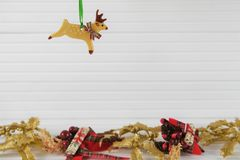 圣诞节挂掉电话面团驯鹿的xmas装饰的摄影图象有在白色木头的欢乐金子xmas背景 免版税图库摄影
