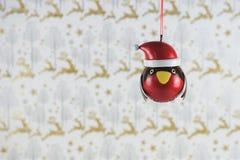 圣诞节摄影图象挂掉电话在帽子的红色知更鸟的圣诞节装饰有驯鹿包装纸背景 免版税库存图片