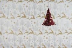 圣诞节摄影图象挂掉电话软的红色衣服饰物之小金属片xmas树的圣诞节装饰有驯鹿包装纸背景 图库摄影