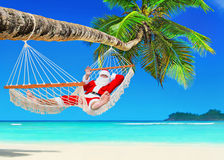 圣诞节放松在吊床的圣诞老人在热带棕榈滩 免版税库存图片