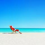 圣诞节放松在sunlounger的圣诞老人在海洋热带b 免版税库存照片