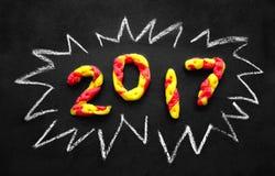 圣诞节数字由红色和黄色彩色塑泥做的2017个新年被隔绝在黑背景 免版税库存图片