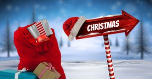 圣诞节文本和礼物与木路标在圣诞节冬天风景和圣诞老人帽子有克里斯的 免版税库存照片