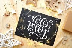 圣诞节文本霍莉愉快地在有圣诞节deoccrusties的一个黑板担任主角,在木背景的诗歌选 平的位置,上面 免版税图库摄影