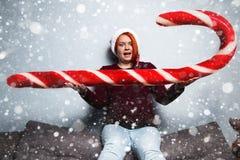 圣诞节新年愉快的妇女在有糖果sti的圣诞老人帽子 免版税图库摄影