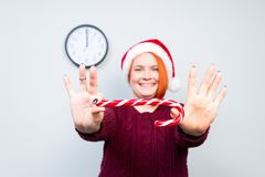 圣诞节新年愉快的妇女在有糖果sti的圣诞老人帽子 免版税库存图片