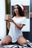 圣诞节新年概念,在圣诞老人帽子的性感的模型有礼物的 图库摄影