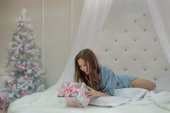 圣诞节早晨女孩醒并且发现一件新年礼物在她床和她上是惊奇和愉快的在圣诞节 免版税库存图片