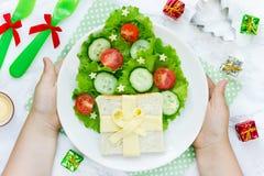 圣诞节早餐孩子递拿着有圣诞节tre的一块板材 免版税库存照片