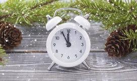 圣诞节时钟是有冬天修剪的一个白色闹钟 木头和锥体 免版税图库摄影