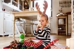 圣诞节时间吹的党口哨的小女孩 免版税库存照片