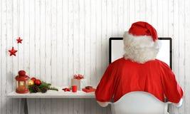 圣诞节时间在圣诞老人室 圣诞老人回答在计算机上的信件 免版税图库摄影
