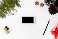圣诞节时间的智能手机构成 锥体和圣诞节装饰在白色背景 库存图片