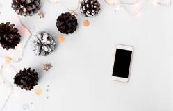 圣诞节时间的智能手机构成 锥体和圣诞节装饰在白色背景 库存照片