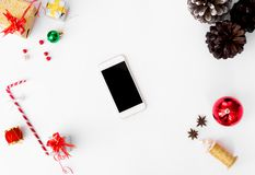 圣诞节时间的智能手机构成 锥体和圣诞节装饰在白色背景 免版税库存图片