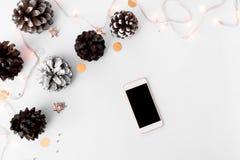 圣诞节时间的智能手机构成 锥体和圣诞节装饰在白色背景 免版税图库摄影