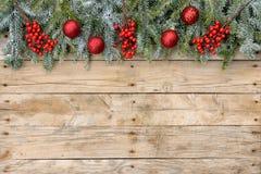圣诞节明信片框架、杉树与红色闪烁球和莓果在概略的木背景贺卡的 自然 库存图片