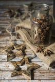 圣诞节星,一个瓶子的诗歌选在一张木老桌上的茴香 库存图片