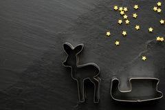 圣诞节曲奇饼切削刀用金黄糖在黑背景担任主角 库存照片