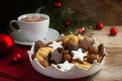 圣诞节曲奇饼和一个咖啡杯用热的可可粉,杉树麸皮 免版税库存照片