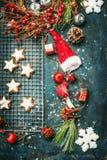 圣诞节曲奇饼和冬天装饰与圣诞老人帽子和花圈在土气木背景 免版税库存照片