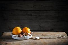 圣诞节曲奇饼和桔子在一个碗在一张土气桌上,黑暗 库存图片
