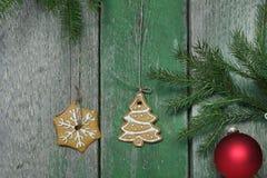 圣诞节曲奇饼在一个绿色木墙壁、冷杉分支和欢乐球附近垂悬 免版税库存图片