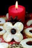 圣诞节曲奇饼在与一个灼烧的蜡烛的背景中 库存照片