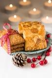 圣诞节曲奇饼ona葡萄酒板材用霍莉莓果和在白色桌上的杉木锥体 库存图片