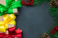 圣诞节有丝带弓和分支圣诞树的礼物盒,锥体和ashberry具体葡萄酒背景 库存照片
