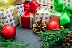 圣诞节有丝带弓的在具体葡萄酒背景的礼物盒和分支圣诞树和红色球玩具和锥体 免版税图库摄影