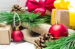 圣诞节有丝带弓的在白色木葡萄酒背景的礼物盒和分支圣诞树和红色球和锥体 免版税库存照片