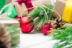 圣诞节有丝带弓的在白色木葡萄酒背景的礼物盒和分支圣诞树和红色球和锥体 库存图片