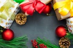 圣诞节有丝带弓的在黑暗的具体葡萄酒背景上面的礼物盒和分支圣诞树和玩具球玩具和锥体竞争 库存图片