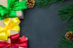 圣诞节有丝带弓的礼物盒和分支在黑暗的具体葡萄酒背景的圣诞树 库存照片