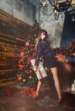 圣诞节有圣诞节礼物的冬天妇女 神仙的美丽的圣诞节和圣诞树欢乐构成 时装模特儿女孩w 免版税库存图片