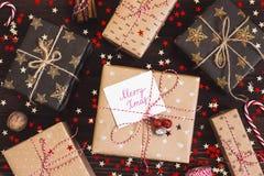 圣诞节有明信片快活的xmas的节日礼物箱子在装饰的欢乐桌上 免版税库存照片